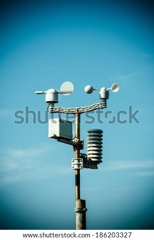 Weather station monitoring equipment against blue sky - stock photo