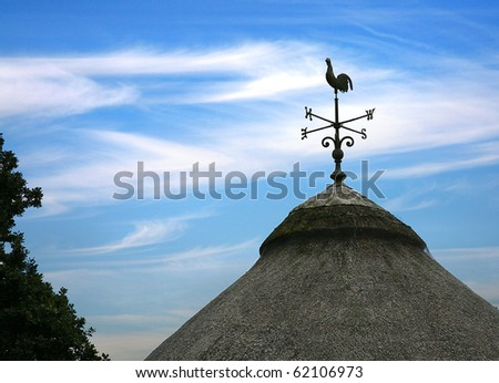 weather vain of cockerel on a traditional thatched roof with blue sky and wispy clouds - stock photo