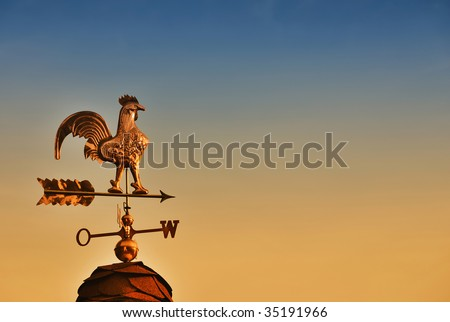Weather Vane against sunset sky with copy space - stock photo