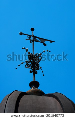 Weather vane opposite the blue sky as the background - stock photo