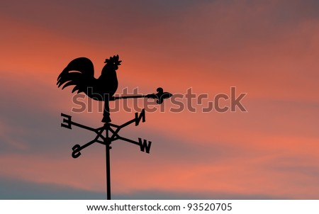 Weathercock silhouetted against sunset - stock photo