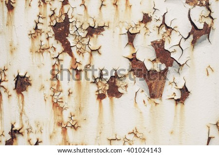 Weathered and worn crusted paint on metal wall background - stock photo