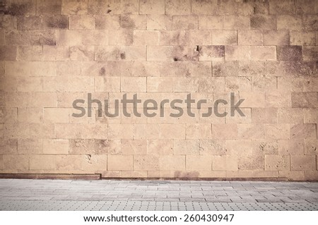Weathered cinder block, brick wall texture with sidewalk. - stock photo