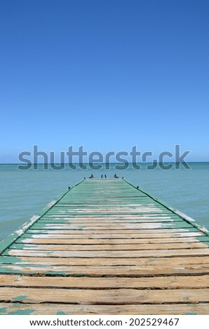weathered dock over tropical blue water - stock photo