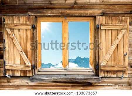 Weathered facade of a mountain hut with mountain  reflection in the window - stock photo