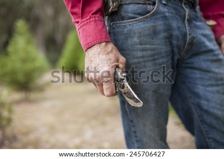 weathered farmer's hands holding pruning shears - stock photo