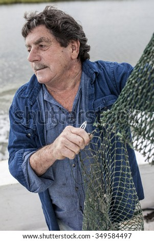 Weathered fisherman mending nets on the deck of a boat - stock photo