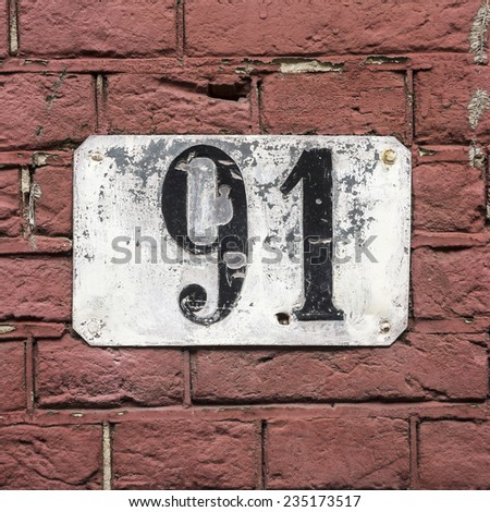 weathered house number ninety one, painted on a metal plate. - stock photo