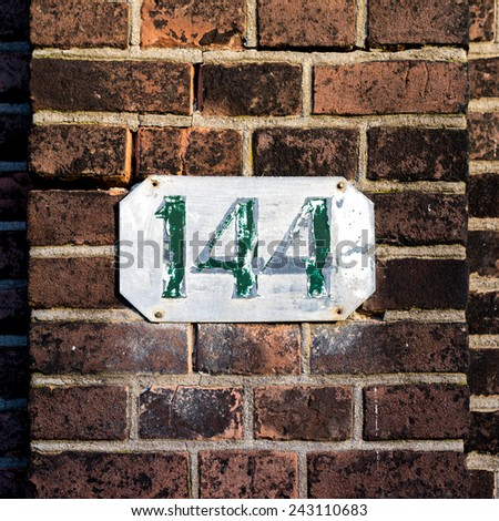 weathered house number one hundred and forty four - stock photo