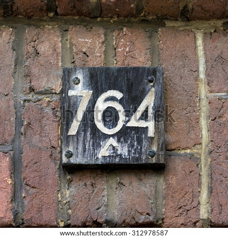 weathered House number seven hundred and sixty four painted on a piece of wood - stock photo