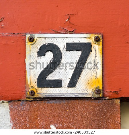 weathered house number twenty seven made of cast aluminum and painted over - stock photo