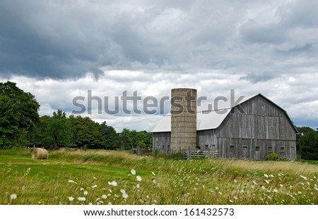 weathered old barn and silo with hay bale in field - stock photo