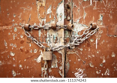 Weathered old door with lock and chain, landscape orientation. - stock photo