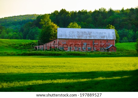 Weathered old red barn in a field of green grass in Stowe, Vermont, USA - stock photo