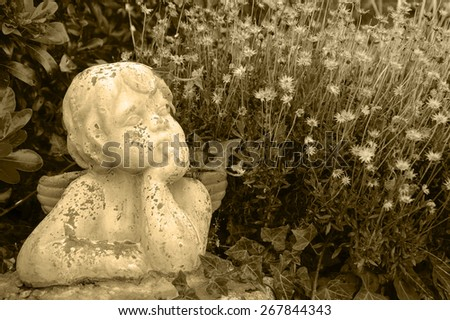 Weathered statue of an infant angel in overgrown garden. Aged monochrome photo. Sepia. - stock photo