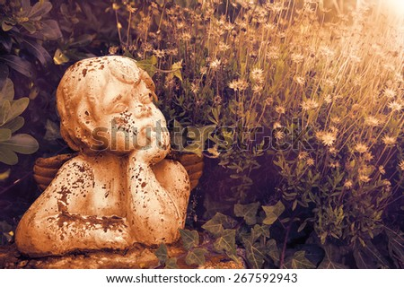 Weathered statue of an infant angel in overgrown garden. Sunset golden light. Toned photo. - stock photo