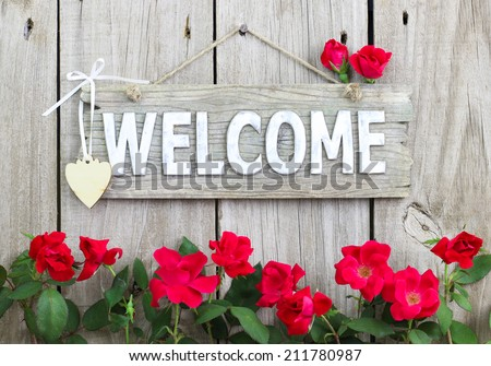 Weathered welcome sign hanging on wood fence with flower border of red roses - stock photo