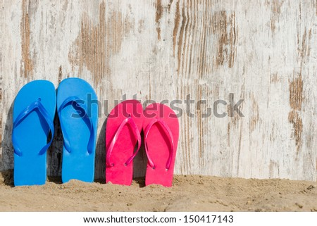 weathered wood on the beach and some slippers - stock photo