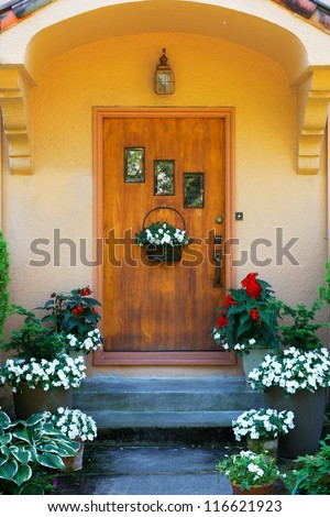 Weathered wood stained home door with three windows and flowers - stock photo