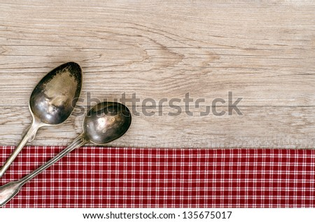 Weathered wood with two silver spoons on a red and white checkered cloth - stock photo