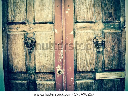 Weathered wooden door with decorative handles - in shape of human head with wreath on it (like Roman patrician). Paris, France. Aged photo. - stock photo