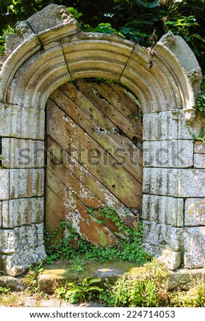Weathered wooden door with rusty decorative key hole. Old farmhouse in Brittany, France.  - stock photo