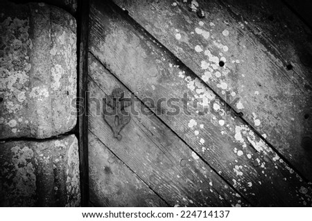Weathered wooden door with rusty decorative key hole. Old farmhouse in Brittany, France. Aged photo. Shadowed angles. Black and white. - stock photo