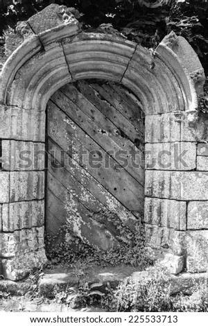 Weathered wooden door with rusty decorative key hole. Old farmhouse in Brittany, France. Aged photo. Black and white. - stock photo
