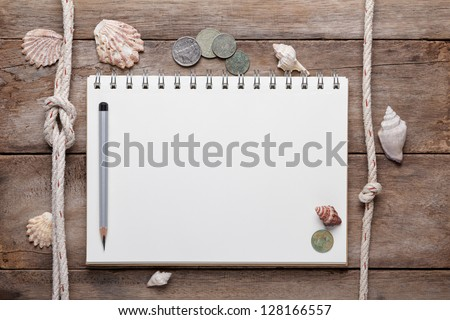 Weathered wooden table with blank notepad, coins and shells - stock photo