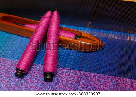 Weaving shuttle with spools of thread on the blue warp - stock photo