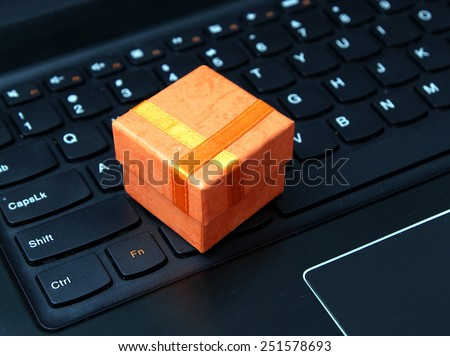 Web shopping / Internet shopping - orange gift box on the black laptop keyboard - stock photo