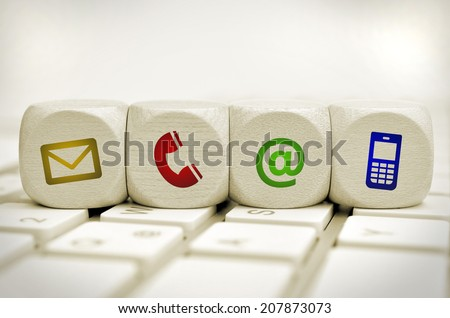 Website and Internet contact us page concept with colored icons on cubes on a keyboard - stock photo