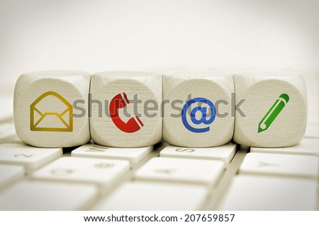 Website and Internet contact us page concept with colored icons on keyboard - stock photo