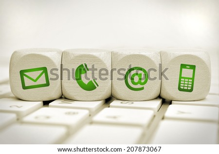 Website and Internet contact us page concept with green icons on cubes on a keyboard - stock photo