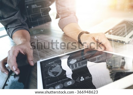 Website designer working digital tablet and computer laptop and graphics design diagram on wooden desk as concept - stock photo
