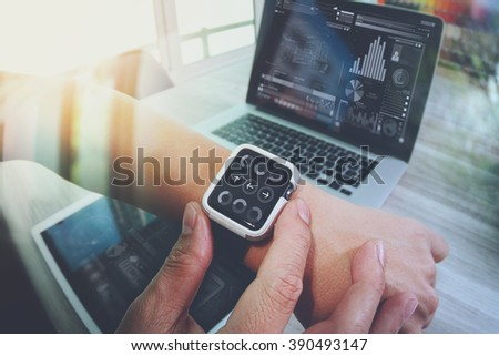 Website designer working with smart watch and digital tablet and digital design diagram on wooden desk as concept - stock photo