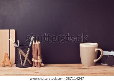 Website header design with designer vintage desk over chalkboard background - stock photo