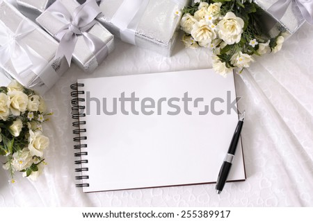 Wedding album or writing book laid on bridal lace with several silver wedding gifts and white rose bouquets.  Wedding list, photo album or thank you note.  Space for copy. - stock photo