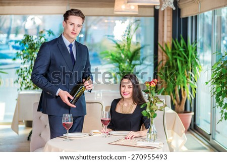 Wedding Anniversary Celebration at the restaurant. Romantic dinner in the restaurant. Young loving couple visiting the restaurant while the man is holding a bottle of wine - stock photo