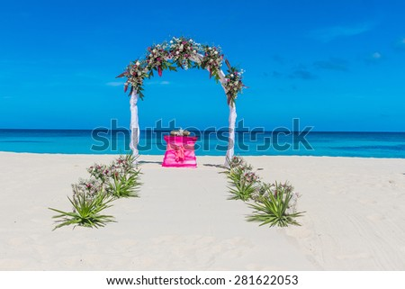 wedding arch and flower decoration, venue, setup on tropical beach, outdoor beach wedding - stock photo