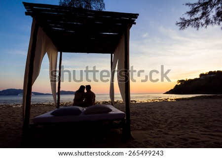 wedding arch and set up on beach, tropical outdoor wedding cabana on beach, wedding table for dinner at sunset - stock photo