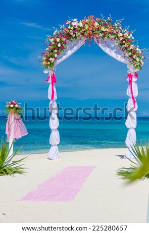 wedding arch, cabana, gazebo on tropical beach decorated with flowers, beach wedding decoration - stock photo