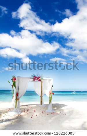 wedding arch decorated with flowers on beach - stock photo
