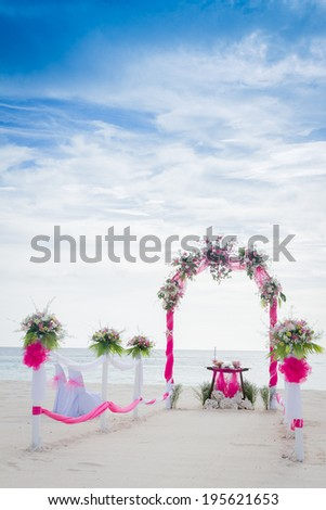 wedding arch decorated with flowers on tropical sand beach, outdoor beach wedding setup - stock photo