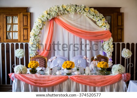 Wedding arch of white flowers decorated wedding table, wedding preparation, serving, empty glasses and plates on the table, yellow flowers - stock photo