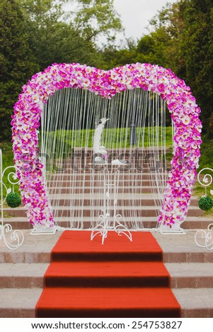 Wedding arch with pink orchid standing on the steps of - stock photo