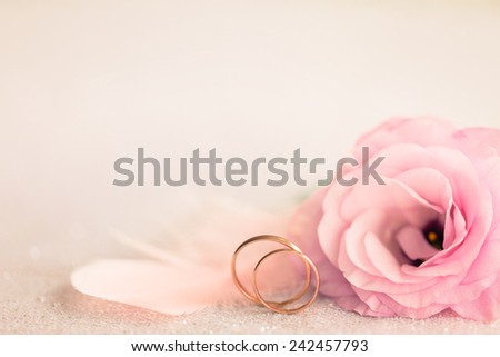Wedding  Background with gold Rings, Eustoma rose flower and light pink feather - stock photo