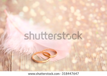 Wedding  Background with Gold Rings, pink feather and golden magical lights  - stock photo