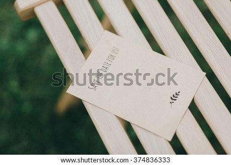 Wedding. Banquet. Decor. Invitation card crafting of cardboard lying on a wooden table - stock photo