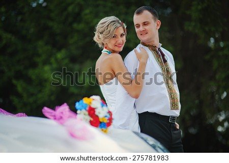 Wedding beautiful couple in traditional dress near exotic supercar - stock photo